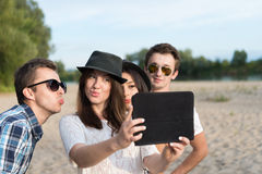 Group Of Young Adult Friends Taking Selfie. Young adult friends taking selfies with tablet and having fun outdoors stock image