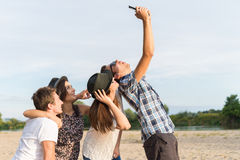 Group Of Young Adult Friends Taking Selfie. Young adult friends taking selfies with tablet and having fun outdoors stock photo
