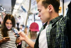 Group of young adult friends using smartphones in the subway royalty free stock photos