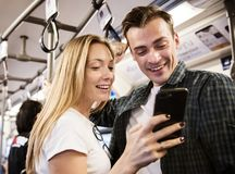 Group of young adult friends using smartphones in the subway stock images