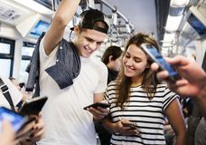 Group of young adult friends using smartphones in the subway Royalty Free Stock Image
