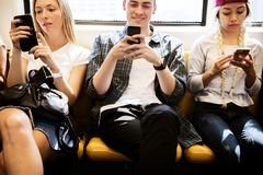 Group of young adult friends using smartphones in the subway stock image