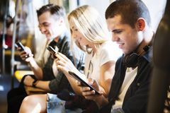 Young adult friends using smartphones. Group of young adult friends using smartphones in the subway royalty free stock images