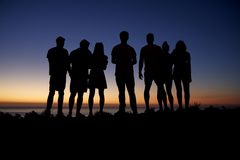 Group of young adults admiring sunset by the seaside Stock Image