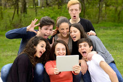 Group of young adults browsing a tablet Stock Photos