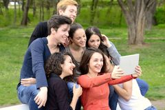 Group of young adults browsing a tablet outside. Group of young adults browsing a tablet and having fun outside Royalty Free Stock Photo