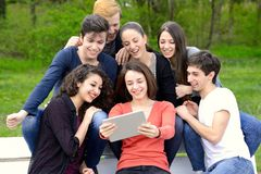 Group of young adults browsing a tablet outside Stock Photography