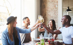 Group of young adults drinking together at table Stock Photos