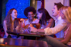 Group of young adults in a nightclub talking. Together around a table stock images