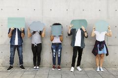 Group of young adults outdoors holding empty placard copyspace t. Hought bubbles stock images
