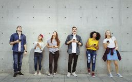 Group of young adults outdoors using smartphones looking up royalty free stock photo