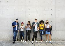 Group of young adults outdoors using smartphones together and ch royalty free stock image