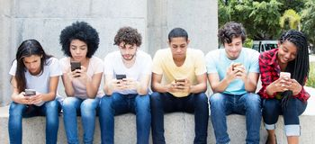 Group of young adults playing online game with phone. Outdoor in the summer Stock Photos