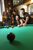 Group of young adults playing pool. Young caucasian woman receiving advice on shooting pool ball while playing billiards Stock Image