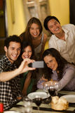 Group of young adults taking a selfie photo. In a restaurant Stock Image