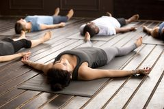 Group of sporty people in Savasana pose. Group of young afro american and caucasian sporty people practicing yoga lesson lying in Dead Body pose, Savasana Royalty Free Stock Photography