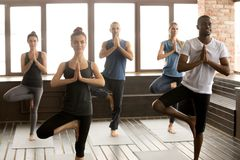 Group of sporty people in Vrksasana pose, close up royalty free stock photography