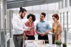 Group of young architects with model of a house standing in office, talking. A group of young architects with tablet and model of a house standing in office royalty free stock image