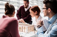 Group of young architects with model of a house standing in office, talking. A group of young architects with model of a house standing in office, working and royalty free stock photos