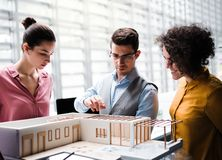 Group of young architects with model of a house standing in office, talking. A group of young architects with model of a house standing in office, working and royalty free stock image