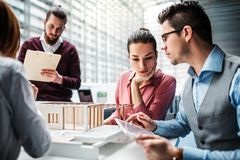 Group of young architects with model of a house standing in office, talking. A group of young architects with model of a house standing in office, working and royalty free stock photo