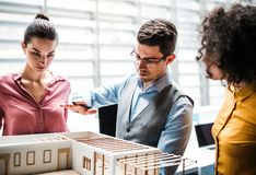 Group of young architects with model of a house standing in office, talking. A group of young architects with model of a house standing in office, working and royalty free stock photography