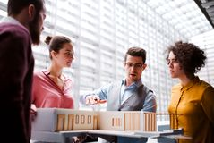 Group of young architects with model of a house standing in office, talking. A group of young architects with model of a house standing in office, working and stock photos