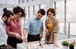Group of young architects with model of a house standing in office, talking. A group of young architects with model of a house standing in office, working and royalty free stock images