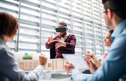 Group of young architects with model of a house and VR goggles working in office. A group of young architects with model of a house and VR goggles working in royalty free stock image
