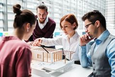 Group of young architects with model of a house working in office, talking. A group of young architects with model of a house working in office, talking royalty free stock image
