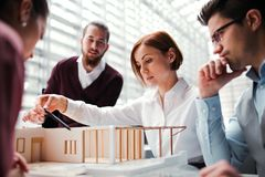 Group of young architects with model of a house working in office, talking. A group of young architects with model of a house working in office, talking stock photography