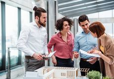Group of young architects with model of a house working in office, talking. A group of young architects with model of a house working in office, talking stock image