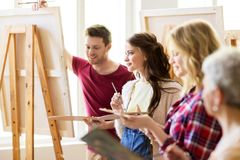 Group of young artists painting at art school. Creativity, education and people concept - group of young artists or students with palettes and paint brushes royalty free stock photos