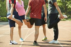 Young asian adults stretching legs on track. Group of young asian adults warming up stretching legs on track Royalty Free Stock Photo
