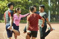 Young asian adults stretching legs on track. Group of young asian adults warming up stretching legs on track Royalty Free Stock Photos