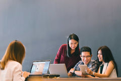 Group of young Asian business colleagues in team casual discussion, startup project business meeting or happy teamwork brainstorm. Concept, with copy space royalty free stock image