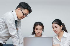 Group of young Asian business people working together on a laptop computer at office. Teamwork brainstroming concept. Selective fo. Cus and shallow depth of Stock Image