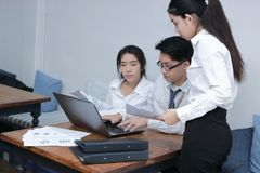 Group of young Asian business people working together with laptop computer at workplace of office. Teamwork brainstroming concept. Selective focus and shallow Royalty Free Stock Photography