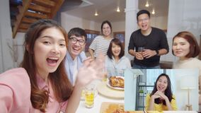 Group of young Asian people look at camera, remote video call greeting with friend at home dinner party