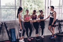 Group of young asian people in sportswear talking after a workout in gym