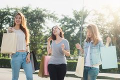 Group of young Asian Woman shopping in an outdoor market with shopping bags in their hands. Young women show what they got in shopping bag under warm sunlight Royalty Free Stock Photo