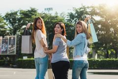 Group of young Asian woman shopping in an outdoor market with shopping bags in their hands. Young women show what they got in shopping bag under warm sunlight Royalty Free Stock Photos
