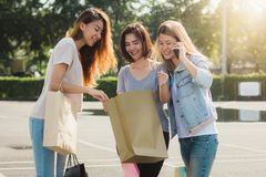 Group of young Asian woman shopping in an outdoor market with shopping bags in their hands. Stock Image