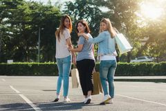 Group of young Asian Woman shopping in an outdoor market with shopping bags in their hands. Young women show what they got in shopping bag under warm sunlight Stock Photos