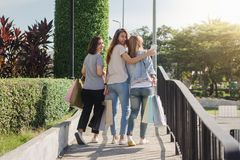 Group of young Asian woman shopping in an outdoor market with shopping bags in their hands. Group of young Asian women shopping in an outdoor market with Royalty Free Stock Photos