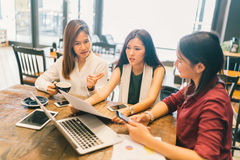Group of young Asian women or college students in serious business meeting or project brainstorm discussion at coffee shop. With laptop computer, digital Stock Photo