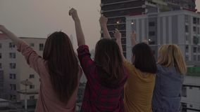 Group of young asian women people dancing and raising their arms up in air to the music played by dj at sunset urban party on roof