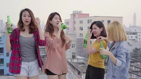 Group of young asian women people dancing and raising their arms up in air to the music played by dj at sunset urban party. Group of young asian women people stock video