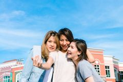 Group of young Asian Women selfie themselves with a phone in a pastel town after shopping. Young women group do outdoor activity under the blue sky. Outdoor Stock Photo