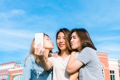 Group of young Asian Women selfie themselves with a phone in a pastel town after shopping. Young women group do outdoor activity under the blue sky. Outdoor Royalty Free Stock Image